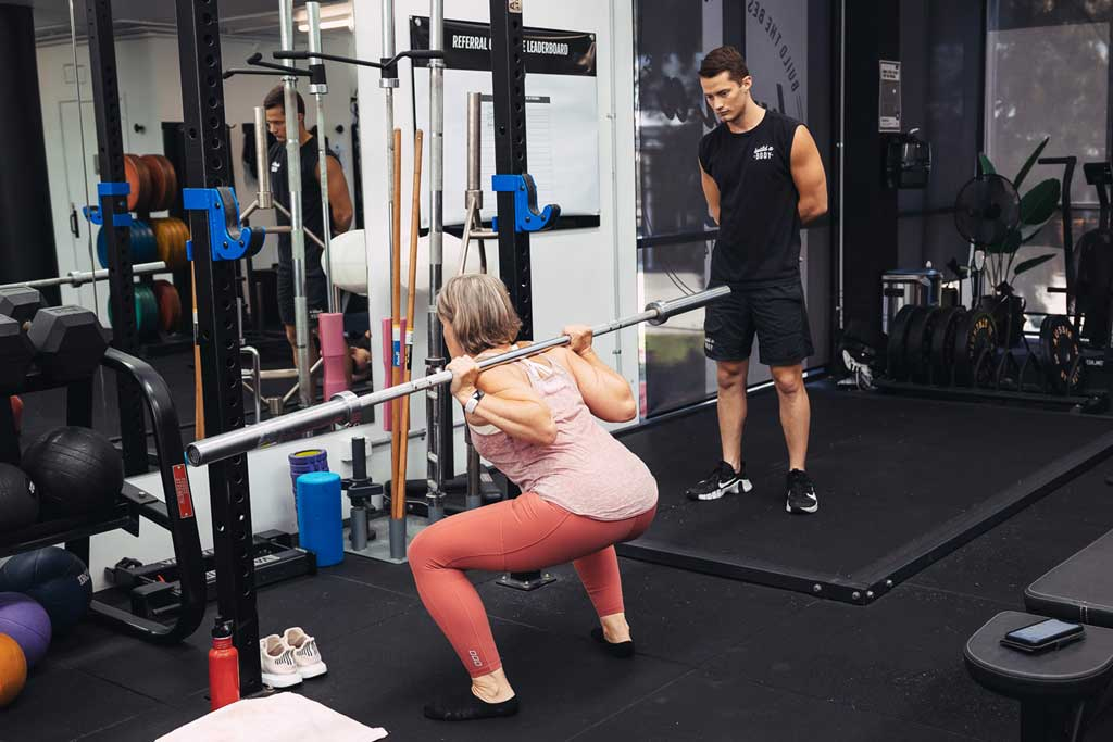 Squats with a bar during personal training session